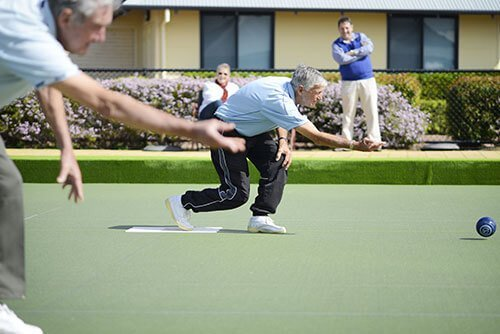Two male retiree residents playing lawn bowls at a St Ives retirement village, with two friends looking on
