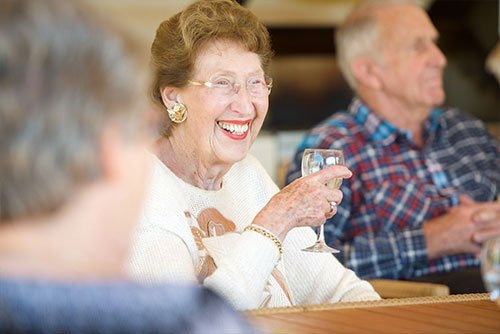 Female resident at St Ives Northshore enjoying a glass of wine with friends