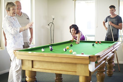 St Ives retired couple with two of their adult children playing pool