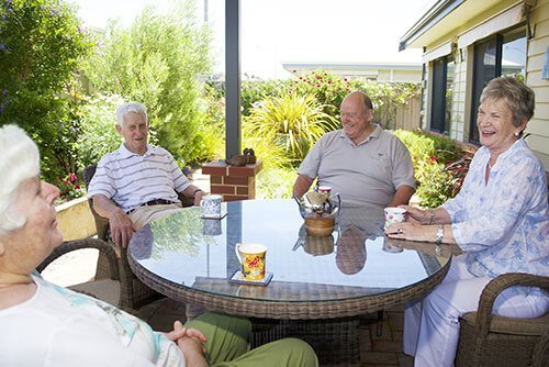 Group of four retirees enjoying a cuppa on their verandah at St Ives Albany
