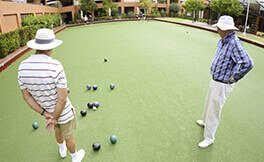 Two males enjoying lawn bowls at a St Ives village