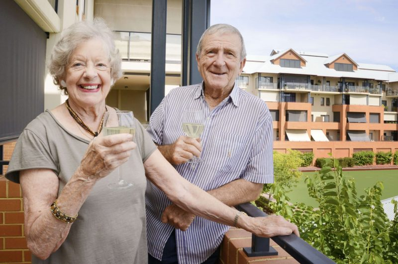 St Ives retired couple enjoying a glass of wine on balcony at St Ives Centro retirement village