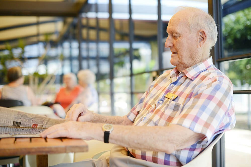 Male retired resident quietly reading the newspaper in the Clubhouse at St Ives Centro retirement village