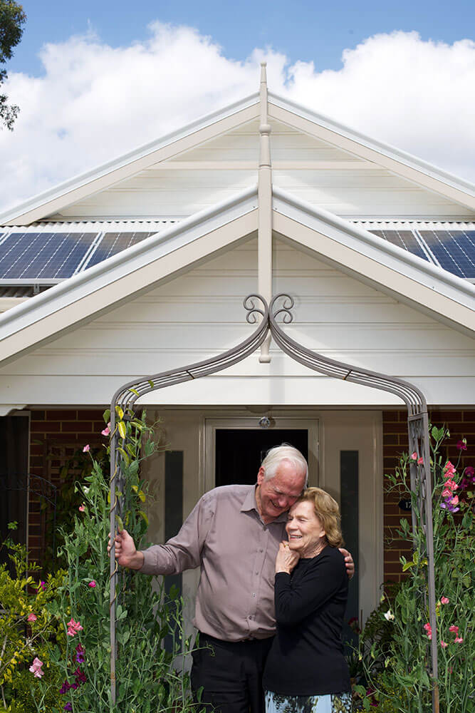 A retired couple at St Ives Lesmurdie retirement village cuddling under the decorative iron atrium arch in front of their home
