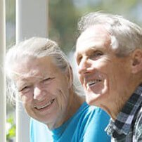 St Ives Lesmurdie resident couple smiling on verandah looking out over their gardens