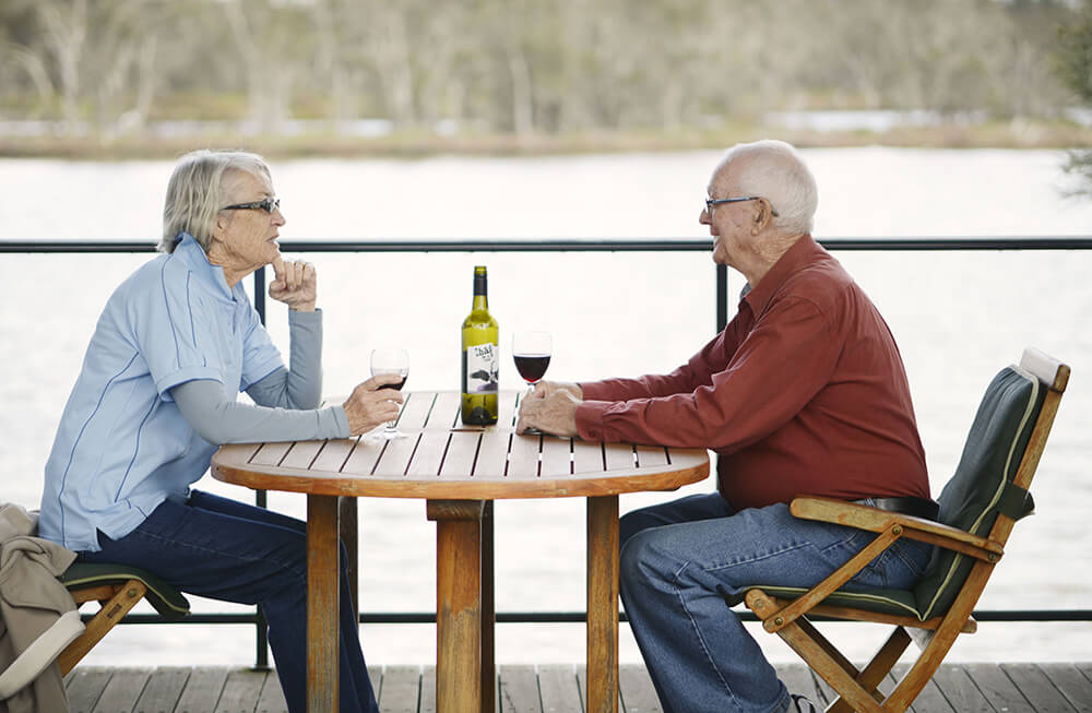 Retired couple enjoying a bottle of red wine overlooking water at St Ives Mandurah retirement village
