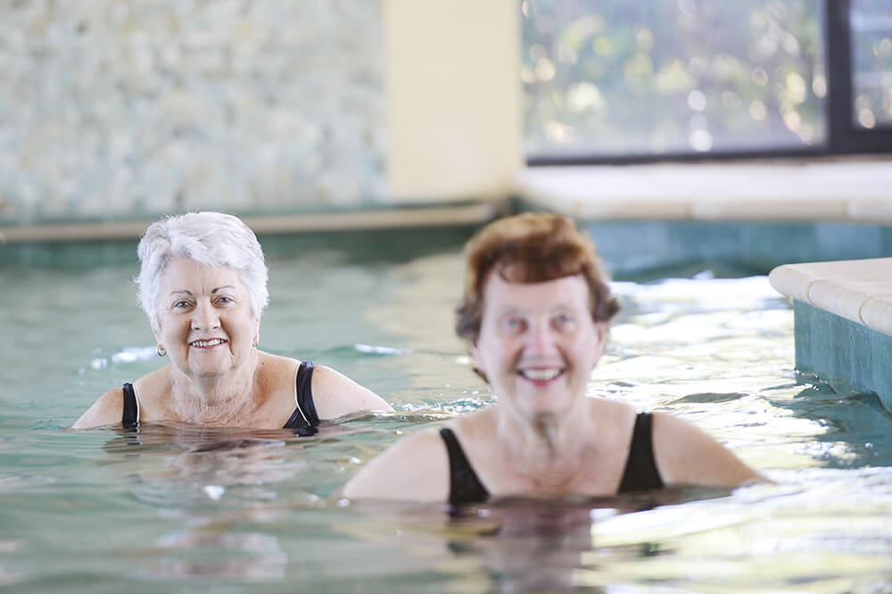 Two female retiree residents at a St Ives village enjoying water aerobics in the pool