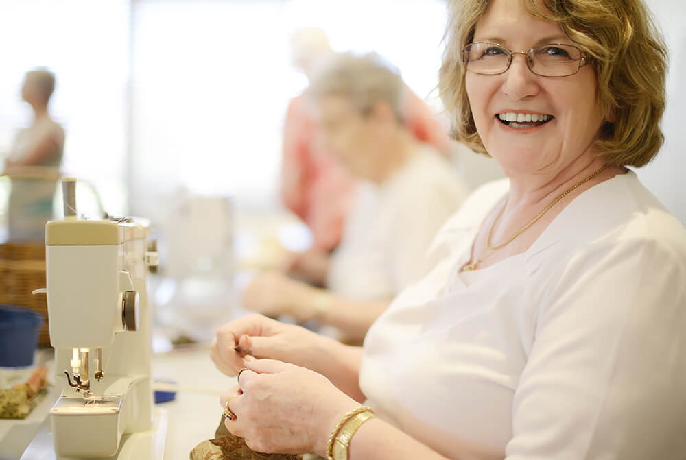 Female retiree resident sewing in the craft room at a St Ives retirement village