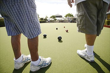 Two male retiree residents playing lawn bowls at a St Ives retirement village