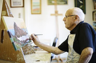 Male retiree resident working on a painting in the art room at a St Ives retirement village