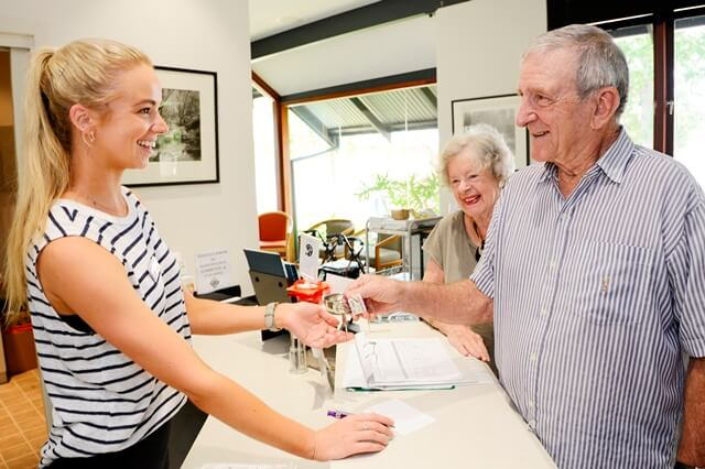 Retired couple at front desk at St Ives Centro retirement village