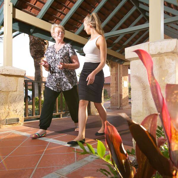 Female retiree resident walking and talking to a staff member at a St Ives retirement village