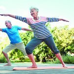 Retiree couple performing a yoga stretch outdoors on yoga mats